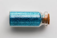 blue glitters in bottle over white background