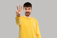 man in yellow sweatshirt showing three fingers