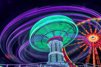 Fun for teens and family. A long exposure of a amusement park with a chain carusel in a very dynamic rotation in the late hours of the day.