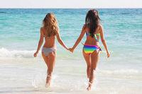 Happy girls running through the water