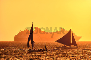Boracay, Philippines - Jan 23, 2020: Sunset on Boracay island. Sailing and other traditional boats with tourists on the sea against the background of the setting sun. Celebrity Millennium cruise ship in the background.