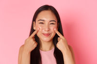 Beauty, fashion and lifestyle concept. Close-up of silly and cute, adorable asian girl poking her cheeks and smiling happily, promo of skincare or makeup product, pink background