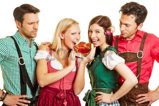 Zwei Frauen essen Brezel vor ihren Männern