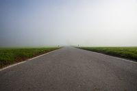road to uncertain destination. converging lines into foggy horizon