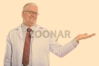 Studio shot of happy mature man doctor smiling while showing something
