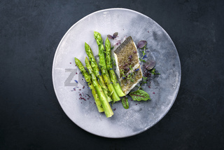 Fried gourmet skrei cod fish filet with green asparagus and lettuce offered as top view on a modern design plate with copy space