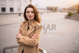 Charming young woman in an autumn beige coat standing leaned with her arms folded with urban city background. Toned photo