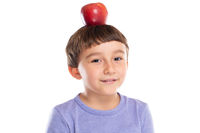 Young boy child with red apple fruit on his head healthy eating concept isolated on white