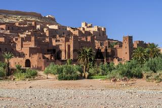 Die Kasbahs von Ait Ben Haddou im Vordergrund stehen zwei Kamele