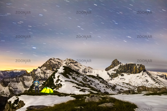 Man standing next to tent under a starry night sky in snowy alpine mountains. Alps, Switzerland.