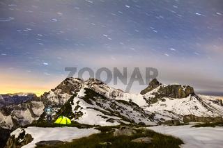 Man standing next to tent under a starry night sky in snowy alpine mountains. Alps, Switzerland.