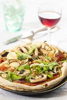 Pilzpizza auf einem Teller mit Rucola
