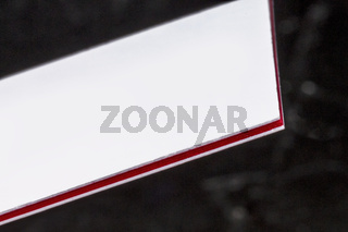 White and red multi-layered thick stock business card, floating on a black background, a mockup