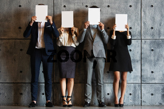 People holding four blank papers