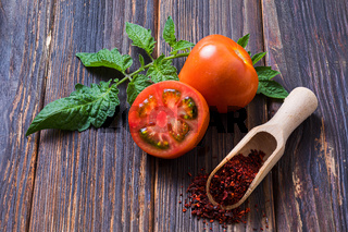 Fresh tomatoes and ground tomato seasoning in wooden scoop