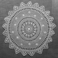 Handmade lace on black background. Macrame fabric lace doily. Crocheted white lace decorative napkin