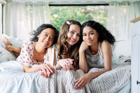 Multi ethnic group of women relax together during summer travel inside the camper van