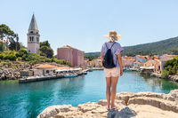 Woman traveler wearing straw summer hat and backpack, standing at edge of the rocky cliff enjoying beautiful panoramic view of Veli Losinj, Losinj island, Croatia