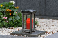 metal  death lantern with glass plates and a burning red candle on a gravestone
