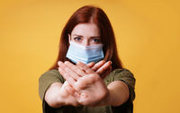 young woman wearing medical face mask making stop hand gesture