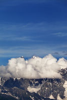 High rocky mountains with snow and glacier hidden in clouds