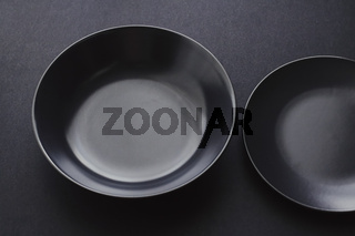 Empty plates on black background, premium dishware for holiday dinner, minimalistic design and diet