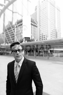 Young handsome blond businessman with eyeglasses thinking in the city outdoors in black and white