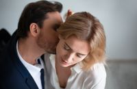 Business man kissing neck of young blonde woman closed eyes. Passion kiss. Enjoyment or workplace romance concept