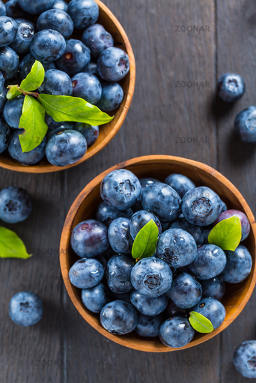 Fresh organic blueberry in bowl on wooden background. Healthy food concept