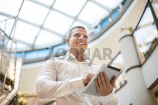 Man with tablet computer in modern business building