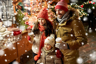 family with takeaway drinks at christmas market