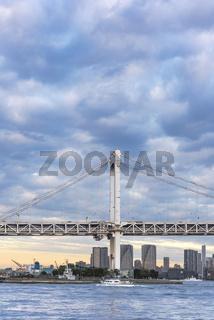 Ship sailing in Odaiba Bay under the Rainbow Bridge of Odaiba bay in Tokyo