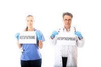 Doctors hold warning signs during Coronavirus COVID-19 virus pandemic