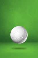 White soccer ball on a green studio background