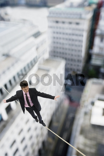 Businessman walking on a tightrope across buildings