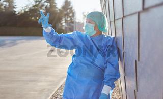 Arzt in Schutzkleidung zeigt Zahl Drei mit Fingern vor Klinik