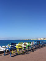 chairs at coastline in nice, France with ocean background