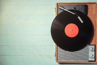 Old turntable with a vinyl record on green wooden table