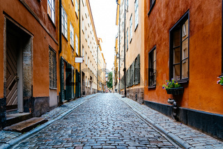 Beautiful old cobblestoned street amidst old colorful houses in Gamla Stan in Stockholm