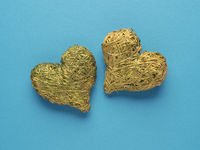 Two hearts made of straw on a blue background