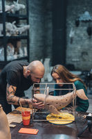 People carefully work on clay whale in workshop