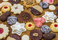 colorful mix of homemade christmas cookies on a dark wooden board