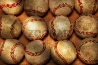 Flat Lay Baseball Still life. A high angle shot of a dozen used baseballs on a wood surface with warm side light.