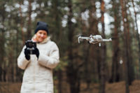 Caucasian woman flying aerial drone in autumn forest. Tech savvy middle age woman. Hobby modern