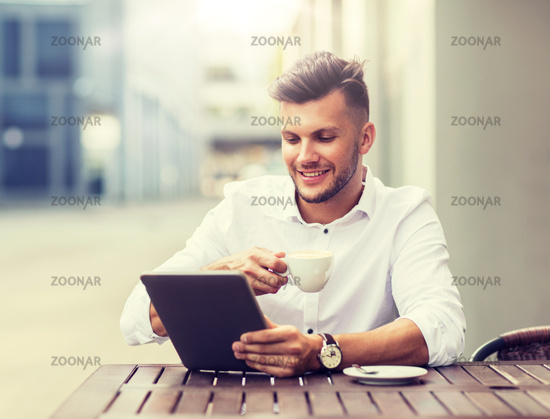 man with tablet pc and coffee at city cafe