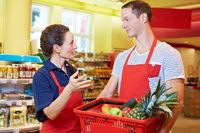 Chefin redet mit Mitarbeiter im Supermarkt