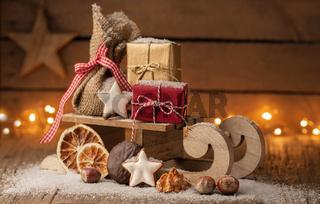 Weihnachtsgruß - Schlitten mit Päckchen auf Holz und Copyspace