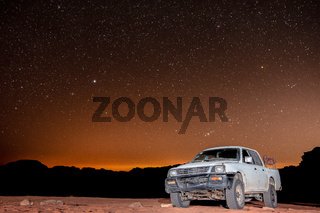 Clear night sky with stars above truck in Wadi Rum desert in Jordan