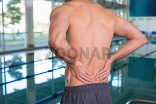 Mid section of shirtless fit swimmer with back ache by pool