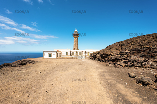 Beautiful view of famous El Faro de Punta Orchilla lighthouse with red volcanic scenery and wide open sea on a sunny day, El Hierro, Canary Islands, Spain
